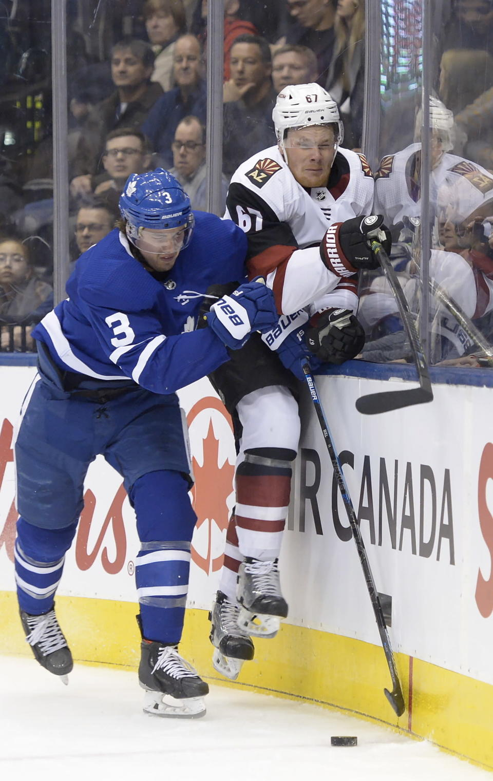 Toronto Maple Leafs defenseman Justin Holl (3) hits Arizona Coyotes left wing Lawson Crouse (67) into the boards during the third period of an NHL hockey game, Tuesday, Feb. 11, 2020 in Toronto. (Nathan Denette/The Canadian Press via AP)