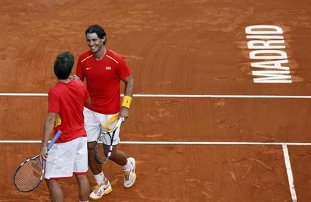 Spain's Rafael Nadal (R) celebrates with teammate Marc Lopez after winning against Ukraine at the end of their Davis Cup World Group playoff doubles tennis match in Madrid September 14, 2013. REUTERS/Sergio Perez