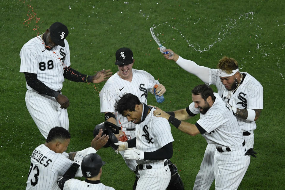 Chicago White Sox's Nick Williams, center, is mobbed by teammates after his fielder's choice scored Nick Madrigal to defeat the Cleveland Indians 4-3 in the ninth inning of a baseball game Monday, April 12, 2021, in Chicago. (AP Photo/Paul Beaty)