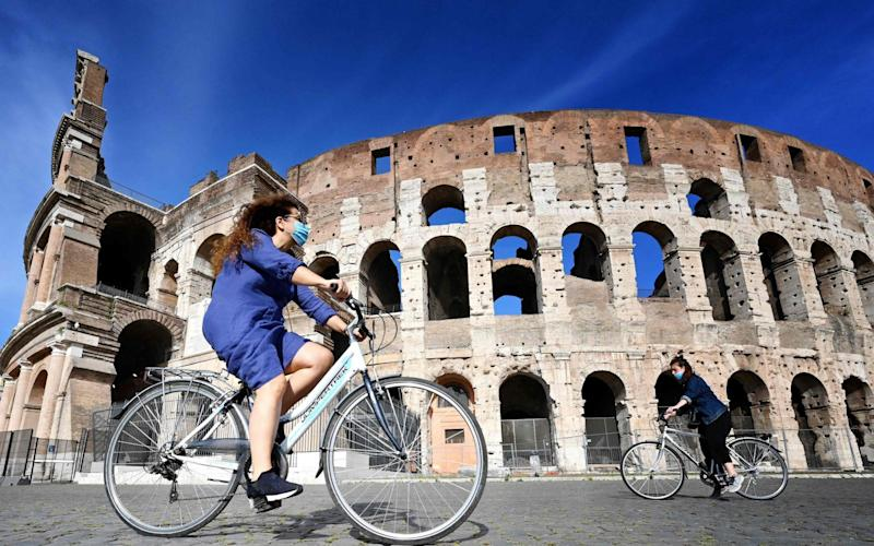 Cyclists ride past the Colosseum during Italy's lockdown - ALBERTO PIZZOLI/AFP