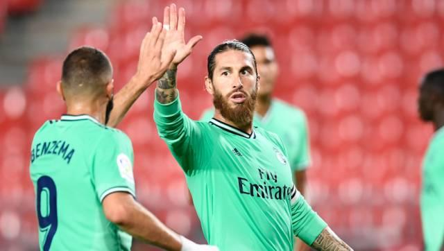 Real Madrid's Sergio Ramos, center, gestures with his teammate Benzema during the Spanish La Liga soccer match between Granada and Real Madrid at the Los Carmenes stadium in Granada, Spain, Monday, July 13, 2020. (AP Photo/Jose Breton)