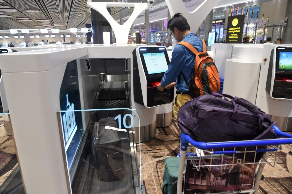 <p>A passenger checks-in his luggage using an automated booth at the newly opened Changi International Airport's Terminal 4 in Singapore (AFP Photo/ROSLAN RAHMAN) </p>