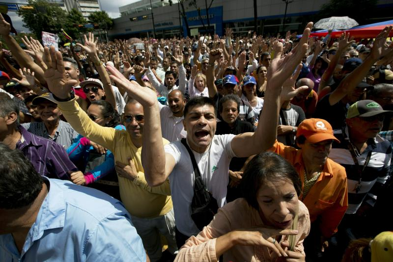 """Opposition members shout """"Guaido President"""" during public a session of National Assembly at a street in Caracas, Venezuela, Friday, Jan. 11, 2019. Juan Guaido, the head of Venezuela's opposition-run congress says that with the nation's backing he's ready to take on Nicolas Maduro's presidential powers and call new elections.(AP Photo/Fernando Llano)"""