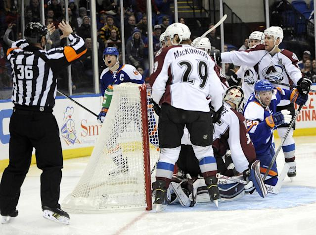 New York Islanders' John Tavares, second from left, reacts to a no goal call by a referee as the Colorado Avalanche stand by in the second period of an NHL hockey game on Saturday, Feb. 8, 2014, in Uniondale, N.Y. (AP Photo/Kathy Kmonicek)