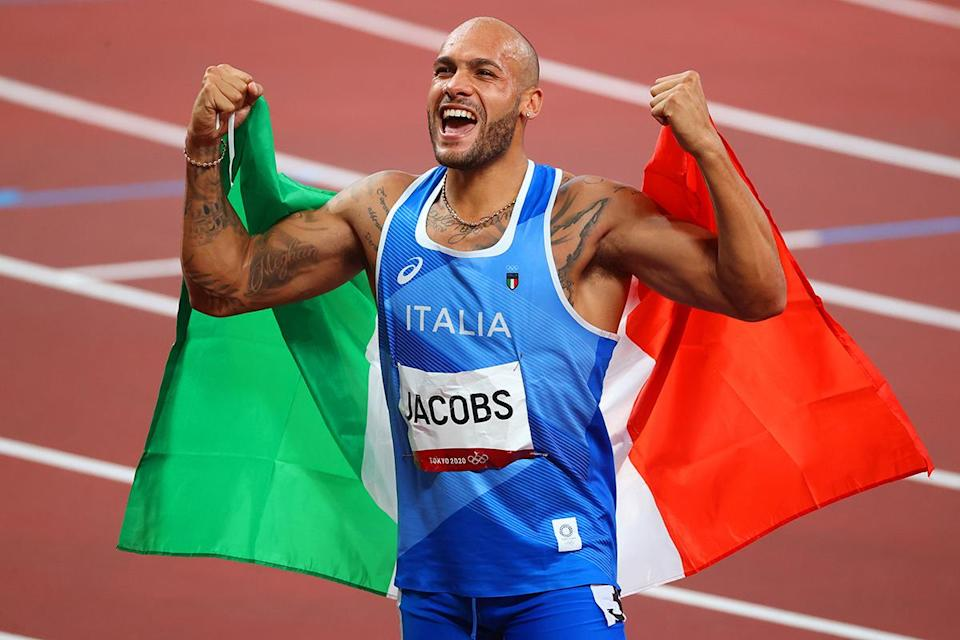 <p>Italy's Lamont Marcell Jacobs celebrates his gold with the Italian flag following the Men's 100m Final at Olympic Stadium on August 1.</p>