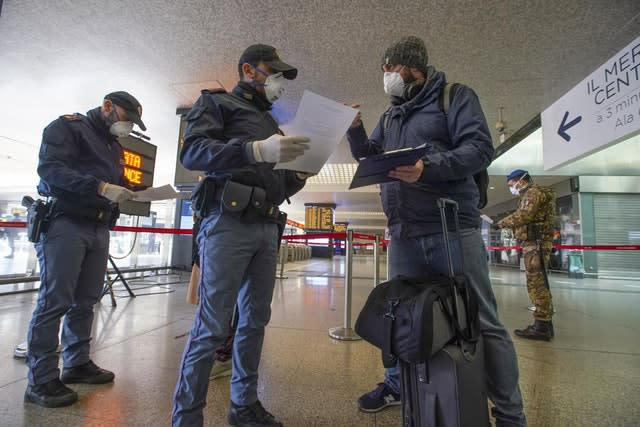 Police check a passenger's travel documents at a Rome train station