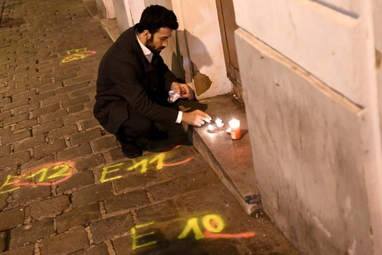 A man lights candles near the scene of the deadly shooting in Vienna