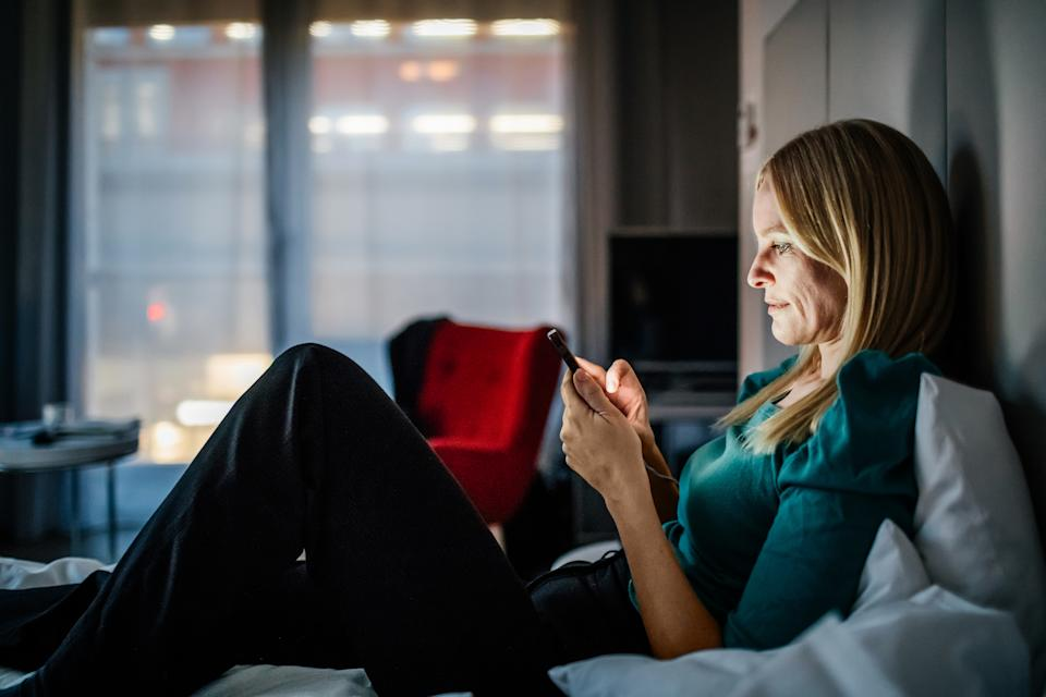 Businesswoman reclining on a hotel bed using her smartphone.