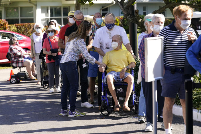 Robert Birkenmeier, center, waits in line with other residents to receive the Pfizer-BioNTech COVID-19 vaccine, Tuesday, Jan. 19, 2021, at John Knox Village in Pompano Beach, Fla. (AP Photo/Lynne Sladky)