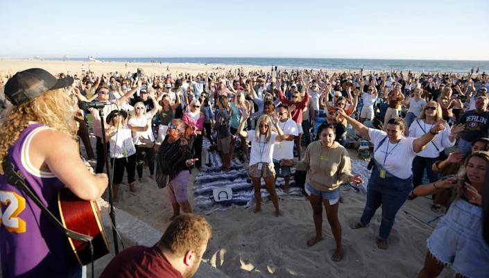Hundreds gathered for the weekly Saturate OC worship event held north of the pier in Huntington Beach, on Friday, July 10, 2020.