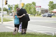 A family whose children went to school with one of the victims pay their respects at the scene