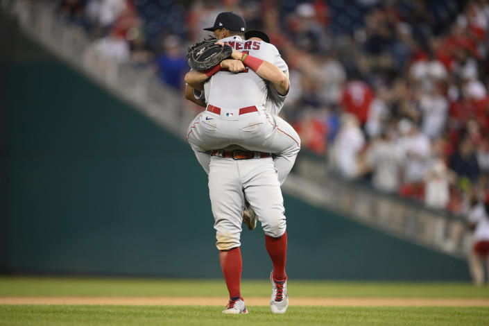 Boston Red Sox's Rafael Devers, front, celebrates with Kyle Schwarber, back, after a baseball game against the Washington Nationals, Sunday, Oct. 3, 2021, in Washington. (AP Photo/Nick Wass)