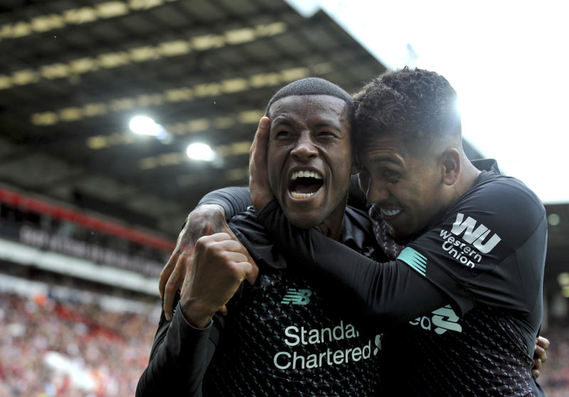 Liverpool's Georginio Wijnaldum, left, celebrates with Liverpool's Roberto Firmino after scoring his side's opening goal during the English Premier League soccer match between Sheffield United and Liverpool at Bramall Lane in Sheffield, England, Saturday, Sept. 28, 2019. (AP Photo/Rui Vieira)