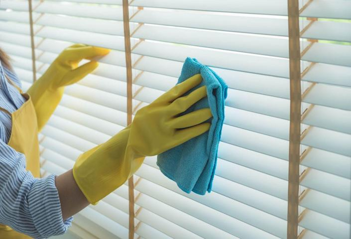 """<p>Don't let your blinds collect dust. According to<em> Country Living</em>, if your blinds are dusty, <a href=""""https://www.countryliving.com/home-maintenance/cleaning/a30899189/how-to-clean-blinds/"""" rel=""""nofollow noopener"""" target=""""_blank"""" data-ylk=""""slk:you will only need a vacuum with the brush attachment, a feather duster, or a microfiber cloth"""" class=""""link rapid-noclick-resp"""">you will only need a vacuum with the brush attachment, a feather duster, or a microfiber cloth</a> to clean them. For wooden slatted or mini blinds, simply shut the blinds and vacuum or wipe the dust away. For any other material, vacuum the front and back of the shades to whisk away dust. </p><p>If a deeper clean is necessary, plastic and metal blinds can be restored using an even mixture of warm water and white vinegar with a few drops of dish soap mixed in. Wet a sponge in the solution, wring it out well, and wipe down each slat. For wood blinds, use furniture polish, and for microfiber or cloth blinds, gently wipe them with a mild soap and warm water solution.</p>"""