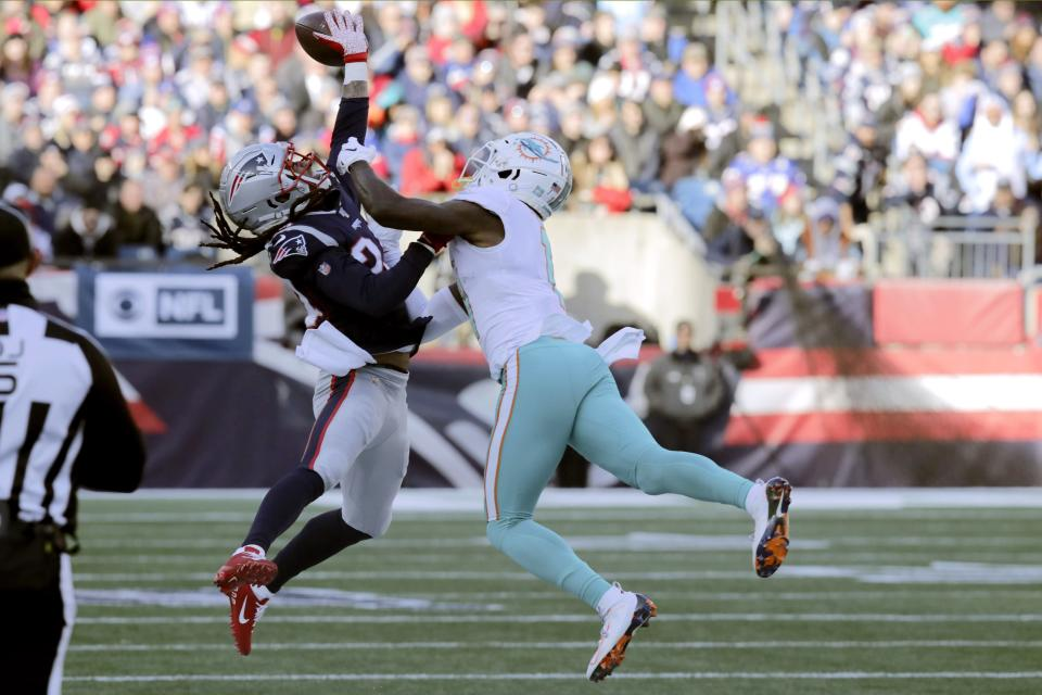 New England Patriots cornerback Stephon Gilmore, left, breaks up a pass intended for Miami Dolphins wide receiver DeVante Parker in the first half of an NFL football game, Sunday, Dec. 29, 2019, in Foxborough, Mass. (AP Photo/Charles Krupa)