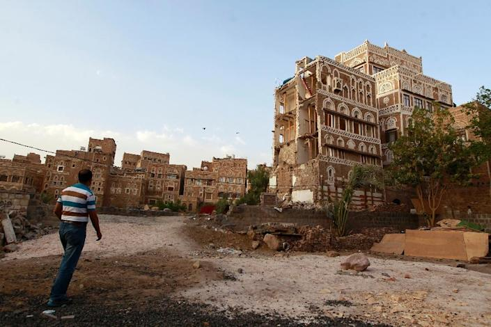 A Yemeni man walks past on March 23, 2016 one of Sanaa's UNESCO-listed buildings that were damaged by air strikes carried out by the Saudi-led coalition over the past year in the Yemeni capital Sanaa (AFP Photo/Mohammed Huwais)