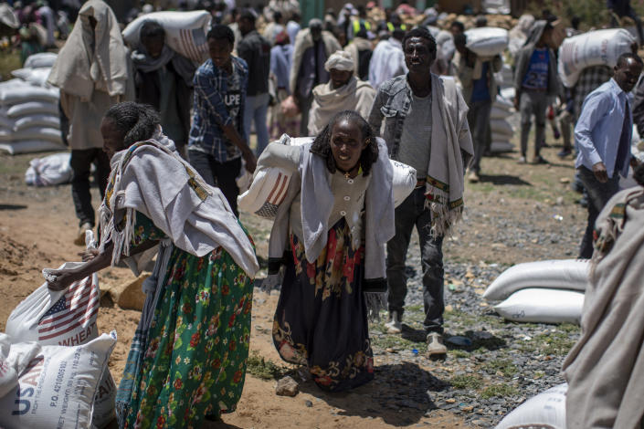 Ethiopian women carry away sacks of wheat after a food distribution by the Relief Society of Tigray in the town of Agula, in the Tigray region of northern Ethiopia, on Saturday, May 8, 2021. (AP Photo/Ben Curtis)