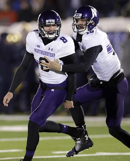 Northwestern kicker Jack Mitchell (8) celebrates with quarterback Christian Salem (18) after a field goal against Notre Dame in overtime of an NCAA college football game in South Bend, Ind., Saturday, Nov. 15, 2014. Northwestern won 43-40. (AP Photo/Nam Y. Huh)