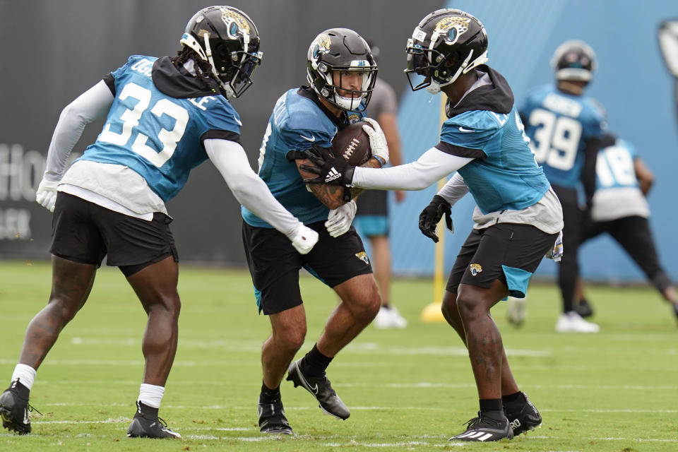 Jacksonville Jaguars running back Nathan Cottrell, center, runs through a drill with running back Dare Ogunbowale (33) and running back Travis Etienne, right, during an NFL football practice, Monday, June 14, 2021, in Jacksonville, Fla. (AP Photo/John Raoux)