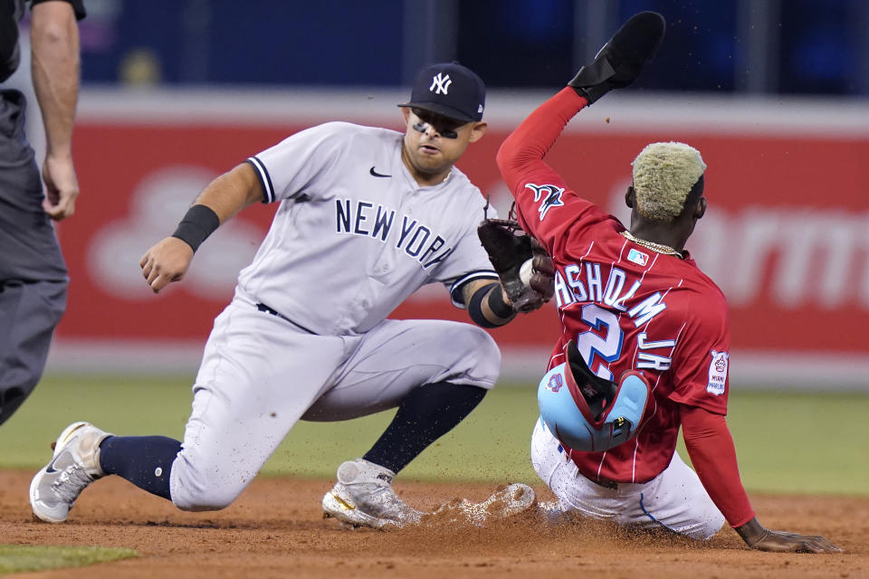 Miami Marlins' Jazz Chisholm (2) is tagged out by New York Yankees second baseman Rougned Odor, left, while stealing second during the third inning of a baseball game, Sunday, Aug. 1, 2021, in Miami. (AP Photo/Lynne Sladky)
