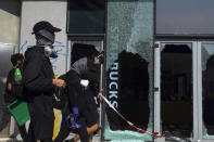 Pro-democracy protesters walk by a vandalized Starbucks cafe on the campus of the Hong Kong Polytechnic University, in Hong Kong, Wednesday, Nov. 13, 2019. Police have increased security around Hong Kong and its university campuses as they brace for more violence after sharp clashes overnight with anti-government protesters. (AP Photo/Vincent Yu)