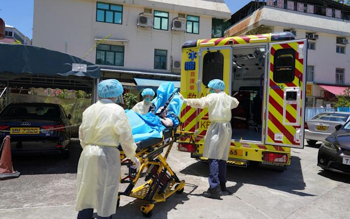 Medical workers carry an elderly man onto an ambulance at a nursing home after 23 people were confirmed to be infected in Hong Kong - China News Service