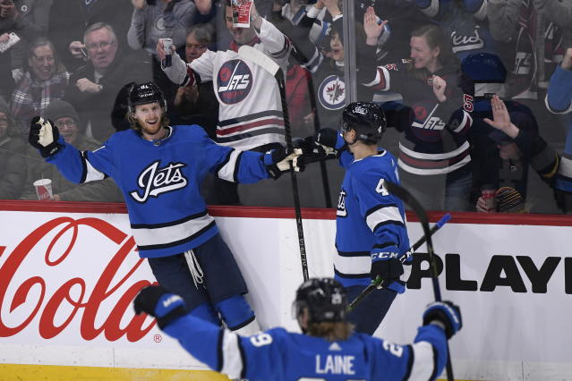 Winnipeg Jets' Kyle Connor (81) celebrates his goal against the Vancouver Canucks with teammates Neal Pionk (4) and Patrik Laine (29) during the first period of an NHL hockey game Tuesday, Jan. 14, 2020, in Winnipeg, Manitoba. (Fred Greenslade/The Canadian Press via AP)