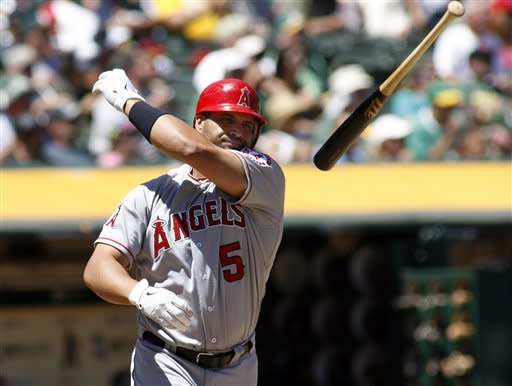 Los Angeles Angels' Albert Pujols throws his bat after flying out against the Oakland Athletics in the third inning of a baseball game in Oakland, Calif., Wednesday, Aug. 8, 2012. (AP Photo/Dino Vournas)
