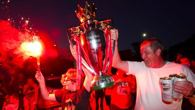 Liverpool fans hold a replica of the Premier League trophy while celebrating their team's title victory. AP