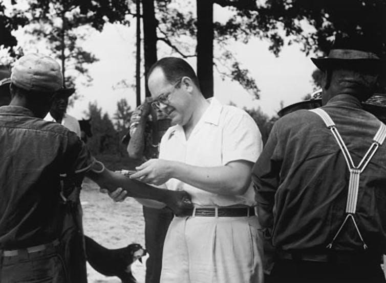 A Black participant in the Tuskegee Syphilis Study has blood drawn by a white man.