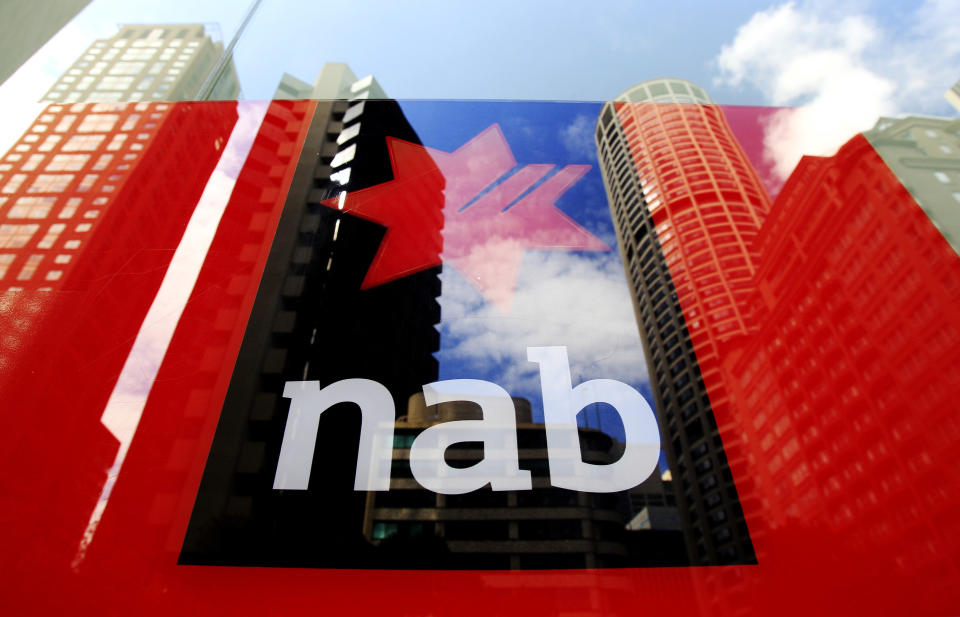 Buildings are reflected in a window at a National Australia Bank branch in Sydney, Australia, Tuesday, Feb. 8, 2011. National Australia Bank, one of the country's largest lenders, reported an 18 percent rise in first quarter cash profit, citing a boost in business lending and fewer bad debts. (AP Photo/Rick Rycroft)