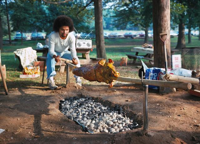 <p>Man roasting a pig. (Photo: Neal Boenzi/NYC Parks Photo Archive/Caters News) </p>