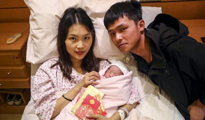 Housewife Zhou Wanli and her husband, construction worker Zheng Fengpei with their baby at Baptist Hospital. Photo: Xiaomei Chen