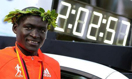 FILE PHOTO: Dennis Kimetto of Kenya poses next to the timekeeping vehicle displaying his new world record, as he celebrates during the awards ceremony for the 41st Berlin marathon, Germany September 28, 2014. REUTERS/Hannibal Hanschke/File Photo
