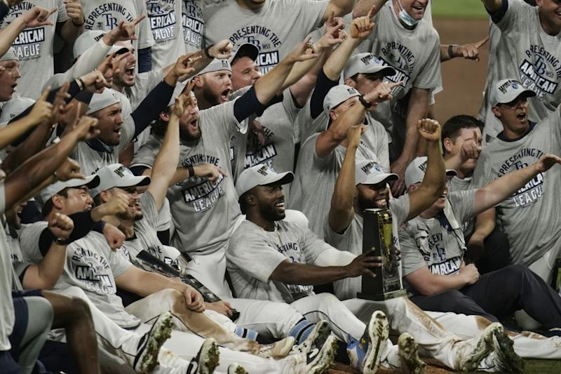 Tampa Bay Rays pose with the American League championship trophy following their victory against the Houston Astros in Game 7 of a baseball American League Championship Series, Saturday, Oct. 17, 2020, in San Diego. The Rays defeated the Astros 4-2 to win the series 4-3 games.(AP Photo/Gregory Bull)