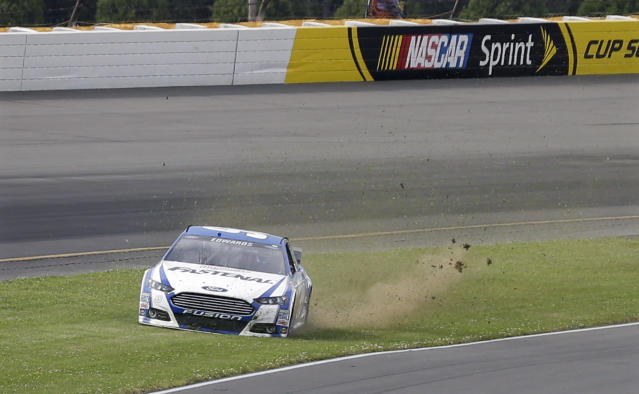 Carl Edwards slides through the grass as he tries to control his car during qualifying for Sunday's NASCAR Sprint Cup Series auto race at Pocono Raceway, Friday, Aug. 1, 2014, Long Pond, Pa. (AP Photo/Mel Evans)