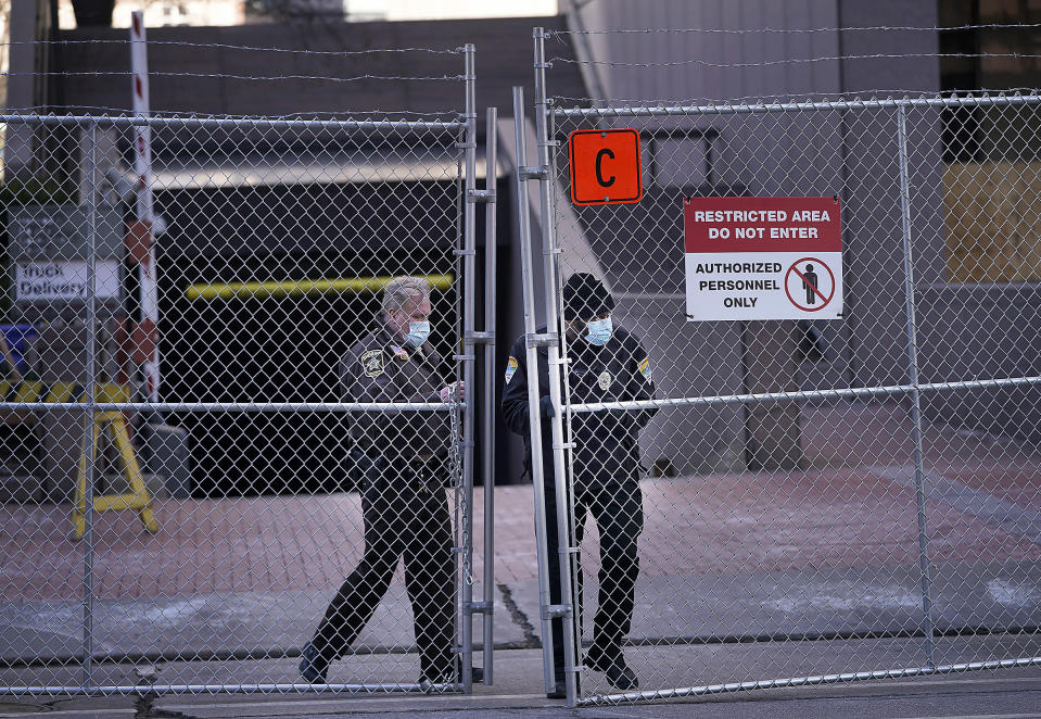 Law enforcement officers open a gate on a fenced perimeter outside the Hennepin County Government Center as preparations continue for the murder trial of former Minneapolis police officer Derek Chauvin which begins Monday and was seen near the Hennepin County Government Center Thursday, March 4, 2021 in Minneapolis. (David Joles/Star Tribune via AP)