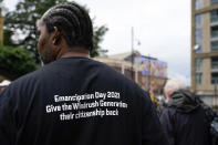 A demonstrator takes part in the annual Afrikan Emancipation Day Reparations march, in Brixton, London, Sunday, Aug. 1, 2021.Black people whose right to live in the U.K. was illegally challenged by the government marked the anniversary Sunday of the act that freed slaves throughout the British Empire, drawing a direct link between slavery and the discrimination they suffered. Dozens of campaigners gathered in Brixton, a center of the Black community in south London, to back the international drive for reparations for the descendants of enslaved Africans and demand legislation to compensate legal residents who were threatened with deportation in what is known as the Windrush Scandal. (AP Photo/Alberto Pezzali)