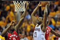 May 19, 2016; Cleveland, OH, USA; Cleveland Cavaliers center Tristan Thompson (13) shoots the ball as Toronto Raptors center Bismack Biyombo (8) and forward DeMarre Carroll (5) defend during the second half in game two of the Eastern conference finals of the NBA Playoffs at Quicken Loans Arena. The Cavaliers won 108-89. Mandatory Credit: Ken Blaze-USA TODAY Sports