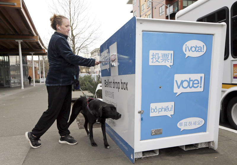 Matilda Jagger with her dog Basil drops off a ballot in the Washington State primary on March 10, 2020 in Seattle. (John Froschauer/AP)