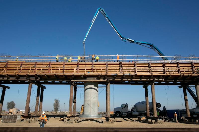 In this photo taken, Wednesday, Dec. 6, 2017, workers pour concrete on to one of the elevated sections of the high-speed rail that will cross over the San Joaquin River, near Fresno, Calif. Officials are raising the projected cost of the first phase of California's bullet train by 35 percent, to $10.6 billion. The extra $2.8 billion comes because of delays in obtaining rights of way and barriers along parts of the track of the 199-mile segment in the Central Valley that is partly under construction. The California High Speed Rail Authority board discussed the increase Tuesday, Jan. 16, 2018. (AP Photo/Rich Pedroncelli)