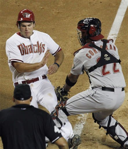 Houston Astros' Carlos Corporan, right, tags out Arizona Diamondbacks' Ryan Wheeler at the plate, as umpire Kerwin Danley watches during the fifth inning in a baseball game Friday, July 20, 2012, in Phoenix. (AP Photo/Ross D. Franklin)