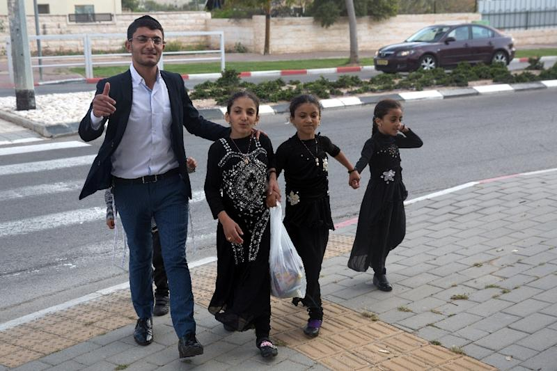 Yemeni Jewish sisters Malka (R), Hodaya(2nd R) and Ester (2nd L) walk alongside their brother Tzion Dahari after the girls arrived to an immigration centre in the Israeli city of Beersheba on March 21, 2016 (AFP Photo/Menahem Kahana)