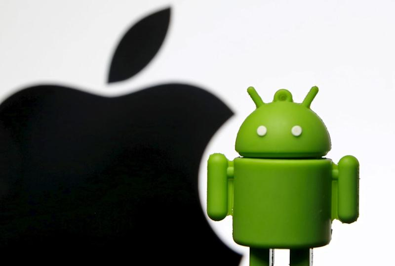 Android mascot is seen in front of a displayed logo of Apple.