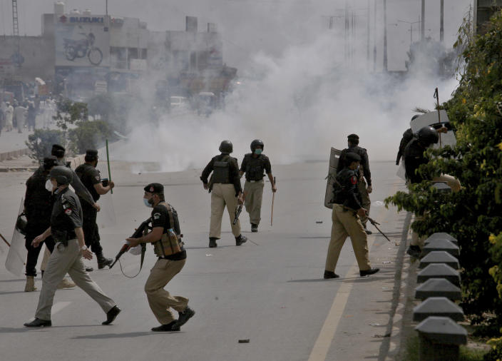 Police fire tear gas to disperse angry supporters of Tehreek-e-Labiak Pakistan, a radical Islamist political party, protesting against the arrest of their party leader, Saad Rizvi, in Peshawar, Pakistan, Tuesday, April 13, 2021. Two demonstrators and a policeman were killed Tuesday in violent clashes between Islamists and police in Pakistan, hours after authorities arrested Rizvi in the eastern city of Lahore, a senior official and local media reported. (AP Photo/Muhammad Sajjad)