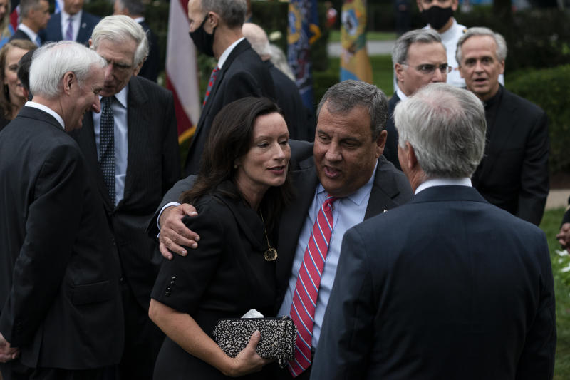 In this Saturday, Sept. 26, 2020, photo former New Jersey Gov. Chris Christie, front second from right, speaks with others after President Donald Trump announces Judge Amy Coney Barrett as his nominee to the Supreme Court in the Rose Garden of the White House, in Washington. Notre Dame President Father John Jenkins stands at back right. (AP Photo/Alex Brandon)