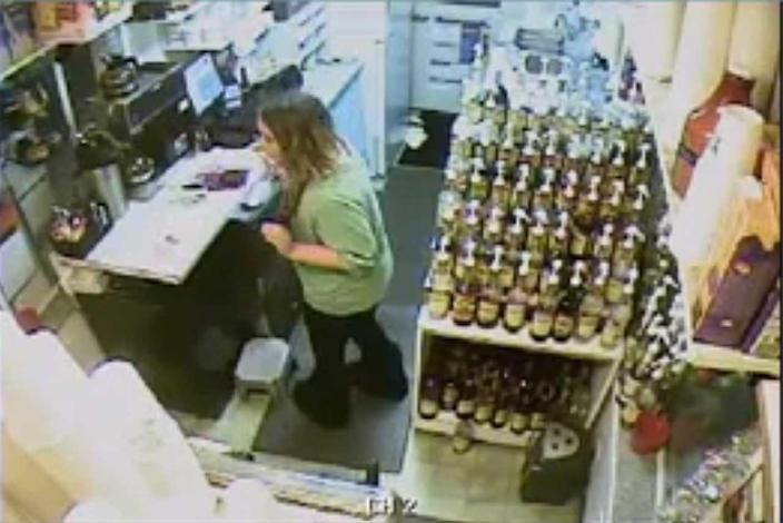 Surveillance video shows Samantha Koenig raising her arms in what looks like a robbery. / Credit: FBI