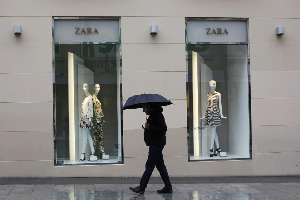 A man walks past a Zara store in central Madrid, March 18, 2015. Spanish group Inditex, owner of the Zara fashion chain, expects to trim investment in 2015 after a recovery in its biggest European markets alongside a store and online expansion boosted profit by five percent. The company's 2014 net profit rose 5 percent to 2.5 billion euros and like-for-like sales rose 5 percent, while overall sales rose 8 percent to 18.12 billion euros, meeting market expectations. REUTERS/Susana Vera (SPAIN - Tags: BUSINESS FASHION)