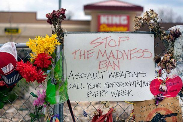 PHOTO: FILE - In this April 23, 2021, file photo, a sign hangs amid the tributes that cover the temporary fence around the King Soopers grocery store in which 10 people died in a mass shooting in late March in Boulder, Colo.  (David Zalubowski/AP)