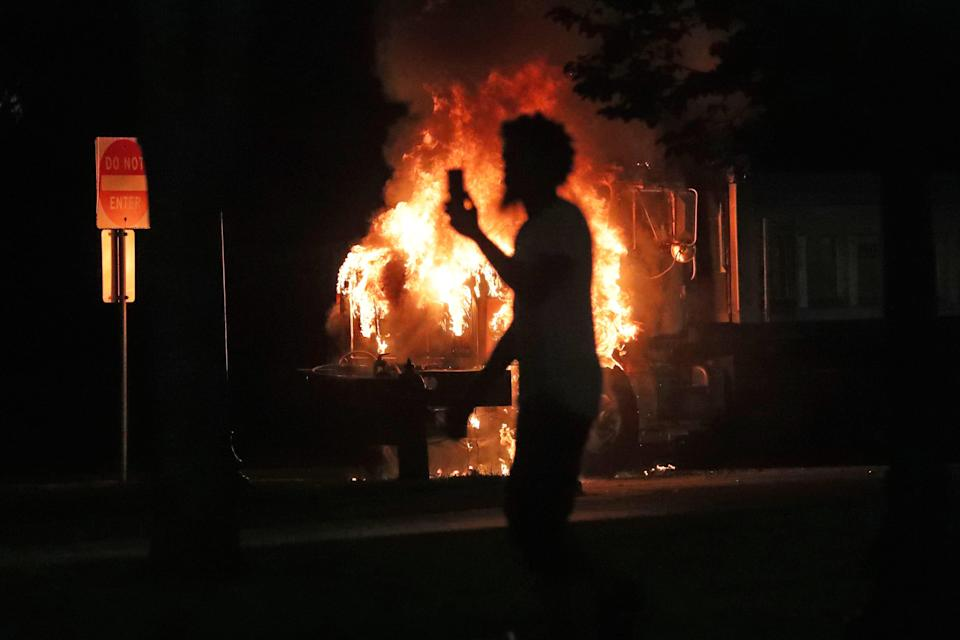 A man records a city truck on fire outside the Kenosha County Courthouse in Kenosha on Sunday, Aug. 23, 2020. Kenosha police shot a man Sunday evening, setting off unrest in the city.